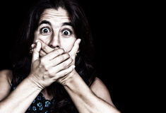 Frightened woman covering her mouth. Grunge image of a frightened woman covering her mouth useful to ilustrate gender violence or discrimination (on a black Royalty Free Stock Images