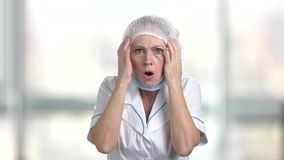 Frightened woman doctor on blurred background. stock footage
