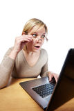 Frightened woman with glasses looking at a laptop Stock Photography