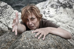 Frightened woman. Hiding behind the rock with an outstretched arm asking for help. Selective focus stock photos