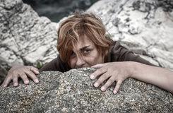 Frightened woman. Hiding behind the rock. Selective focus royalty free stock photography