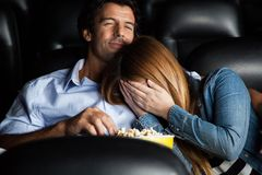 Frightened Woman Leaning On Man In Cinema Theater Royalty Free Stock Photography