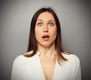 Frightened woman looking at camera. Over dark background royalty free stock photography