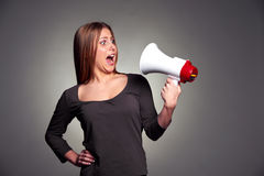 Frightened woman looking on megaphone. Studio shot over dark background Stock Image