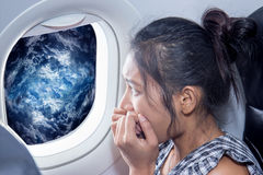 Frightened woman on a plane stock photo