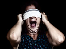 Frightened woman screaming with her eyes covered. Dramatic image of a frightened woman screaming and covering her eyes to avoid seeing isolated on black (useful stock image