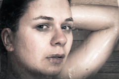 Frightened woman in shower. Photo of young frightened woman through wet glass of shower Royalty Free Stock Photography