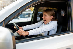 Frightened woman sitting in the car. And holding for the wheel Royalty Free Stock Photography