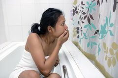 Frightened woman in bathroom. Frightened woman sitting in the tub behind the curtain Royalty Free Stock Photos