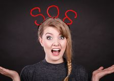 Frightened woman with sos help sign. Fear and fright. Young blonde terrified woman needs help. Frightened hopeless female with red sos sign symbol on dark Royalty Free Stock Photo
