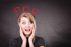 Frightened woman with sos help sign. Fear and fright. Young blonde terrified woman needs help. Frightened hopeless female with red sos sign symbol on dark Stock Photos