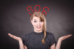 Frightened woman with sos help sign. Fear and fright. Young blonde terrified woman needs help. Frightened hopeless female with red sos sign symbol on dark Royalty Free Stock Photography