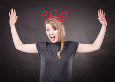 Frightened woman with sos help sign. Fear and fright. Young blonde terrified woman needs help. Frightened hopeless female with red sos sign symbol on dark Stock Image