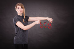 Frightened woman with sos help sign. Fear and fright. Young blonde terrified woman needs help. Frightened hopeless female with red sos sign symbol on dark Stock Images