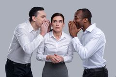 Frightened woman and two men whispering in her ears. Gossiping. Beautiful frightened dark-haired young women standing between two men and listening to them and Stock Photo