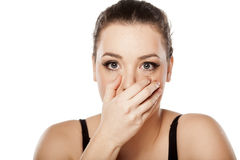 Frightened woman. Frightened young woman covering her mouth with her hand on a white background Royalty Free Stock Images