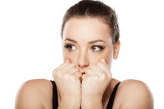 Frightened woman. Frightened young woman covering her mouth with her hands on white background Stock Photos