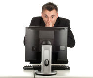 Frightened young businessman working on computer Royalty Free Stock Photography