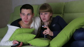 Frightened young couple with glass of wine watching the horrors on television. stock footage
