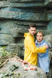 frightened young couple in raincoats terrified stock photo