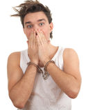 Frightened young man with handcuffed hands Stock Images