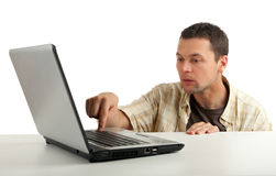 Frightened young man with laptop Royalty Free Stock Photography