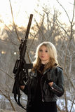 Frightened young woman with a rifle. In winter forest Stock Photo