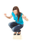 Frightened young woman squat on the pile of books Stock Image