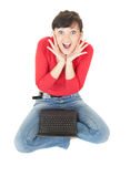 Frightened young woman using laptop, full length Stock Photo