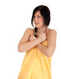 Frightened young woman in yellow towel Stock Photos