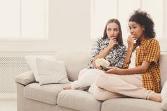 Frightened young women watching TV at home. Frightened young women relaxing and watching scary movie at home, female friends having rest after hard week, copy Stock Images