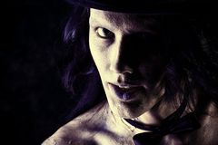 Frightening. Close-up portrait of a gloomy vampire standing at the night background. Halloween Stock Photo