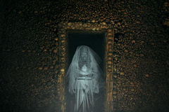 Frightening ghost in a catacomb full of bones. And skulls. Horror and halloween Stock Photo