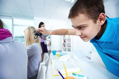 Frightening girls. Evil lad with black spider going to frighten his classmates at lesson Royalty Free Stock Photo