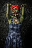 Frightening pin-up zombie. Girl over dark background.  Body-painting project. Halloween make-up. Horror Stock Images