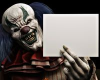 Free Frightening Scary Clown With Sharp Fangs Piercing The Darkness Holding A Black Advertisement Card With Room For Your Text Royalty Free Stock Photos - 158615038