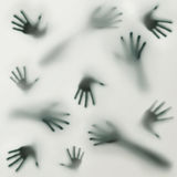 A frightening silhouette of many different hands. A dark and frightening silhouette of many different hands on a foggy moisture glass background stock image
