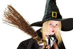 Frightening witch. Portrait of girl in halloween costume and broom with frightening expression royalty free stock photo