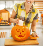 Housewife putting candle inside orange pumpkin Jack-O-Lantern Royalty Free Stock Images