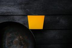 Frigideira chinesa asiático - bandeja oriental tradicional em um fundo de madeira preto Com uma caixa para macarronetes Vista sup Fotografia de Stock Royalty Free