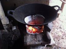 Frigideira chinesa do ferro fundido no fogo do carvão vegetal Fotos de Stock