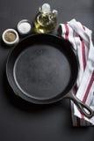 Frigideira do ferro fundido com área da cópia no fundo preto com ingredientes Foto de Stock Royalty Free