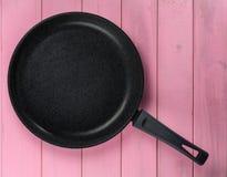 Frigideira do ferro fundido com revestimento da não-vara contra um fundo da textura de madeira cor-de-rosa imagem de stock royalty free