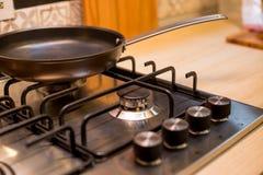 A frigideira nova nos painéis brandnew do fogão de gás Fogão de gás clássico de quatro queimadores com botões de bronze Foco sele fotografia de stock