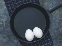 A frigideira preta do ferro fundido no pano preto, a galinha branca eggs B Imagens de Stock