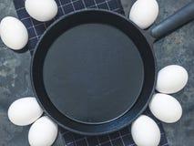 A frigideira preta do ferro fundido no pano preto, a galinha branca eggs B Fotos de Stock