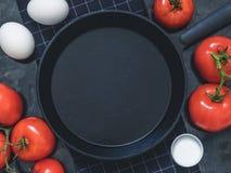 A frigideira preta do ferro fundido no pano preto, a galinha branca eggs, r Imagem de Stock Royalty Free