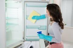 Frigorifero di pulizia della donna con lo straccio Fotografie Stock Libere da Diritti