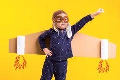 Frihet flickan som spelar för att vara flygplanpiloten, rolig liten flicka med flygarelocket och exponeringsglas, bär vingar som  Arkivbild