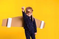 Frihet flickan som spelar för att vara flygplanpiloten, rolig liten flicka med flygarelocket och exponeringsglas, bär vingar som  Arkivfoto